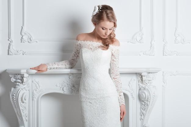 Piękna panna młoda w sukni ślubnej stojąca w eleganckim pokoju hotelowym