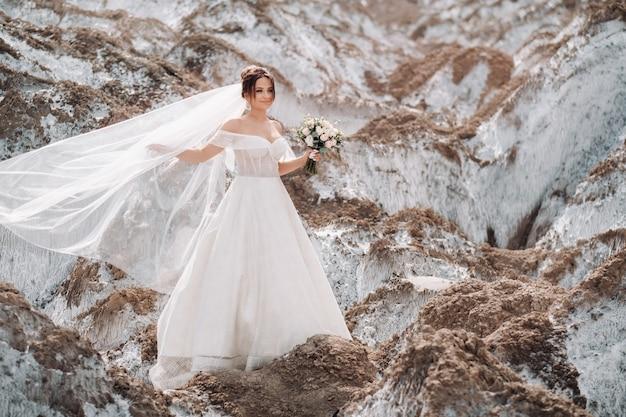 Piękna panna młoda w sukni ślubnej z bukietem na szczycie gór solnych