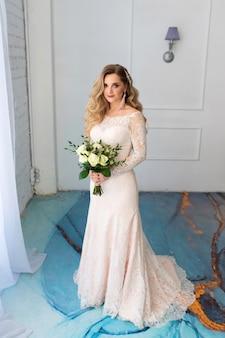 Piękna panna młoda w sukni ślubnej z bukietem w hotelu