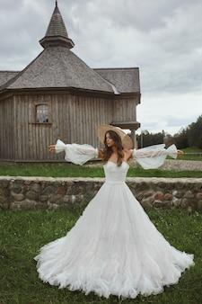 Piękna panna młoda w sukni vintage z długimi rękawami w dniu ślubu na wsi.