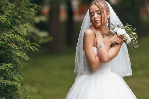 Piękna panna młoda w wspaniałej sukni ślubnej pozującej wśród zieleni na ulicy. dvushka pozuje w sukni ślubnej na reklamę. koncepcja panny młodej dla sukienek reklamowych