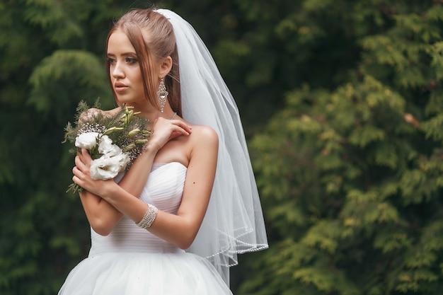Piękna panna młoda w wspaniałej sukni ślubnej pozującej wśród zieleni na ulicy. koncepcja panny młodej dla sukienek reklamowych