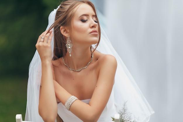 Piękna panna młoda we wspaniałej sukni ślubnej pozuje wśród zieleni na ulicy. dziewczyna pozuje w sukni ślubnej do reklamy. koncepcja panny młodej dla sukienek reklamowych.
