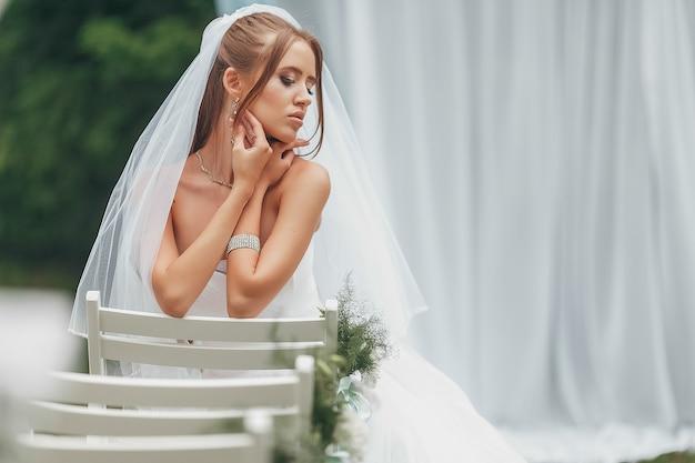Piękna panna młoda we wspaniałej sukni ślubnej pozuje wśród zieleni na ulicy. dziewczyna pozuje w sukni ślubnej do reklamy. koncepcja panny młodej na sukienki reklamowe.