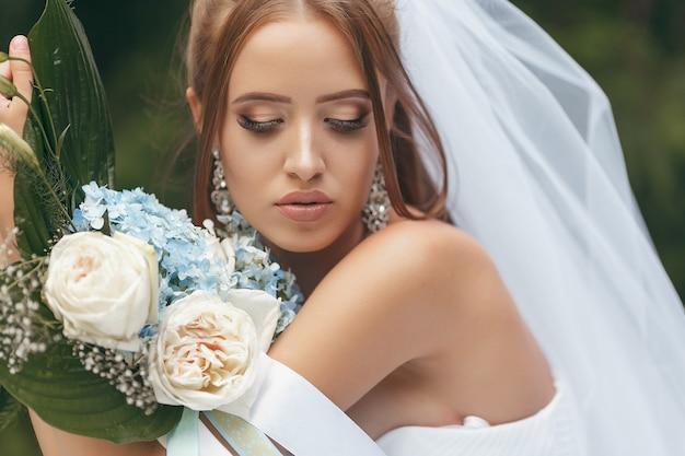 Piękna panna młoda we wspaniałej sukni ślubnej pozuje wśród zieleni na ulicy. koncepcja panny młodej na sukienki reklamowe