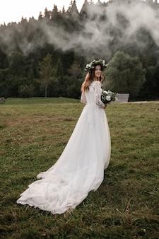 Piękna panna młoda z bukietem i wieńcem na głowie patrząc w kamerę. panna młoda w polu jesienią.
