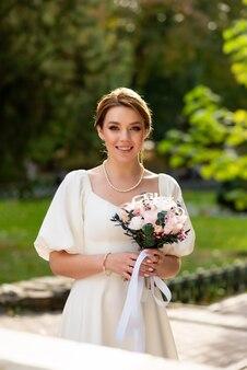 Piękna panna młoda z bukietem kwiatów ślubnych atrakcyjna kobieta w sukni ślubnej