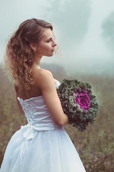 Piękna panna młoda z bukietem na tle mglistego pola