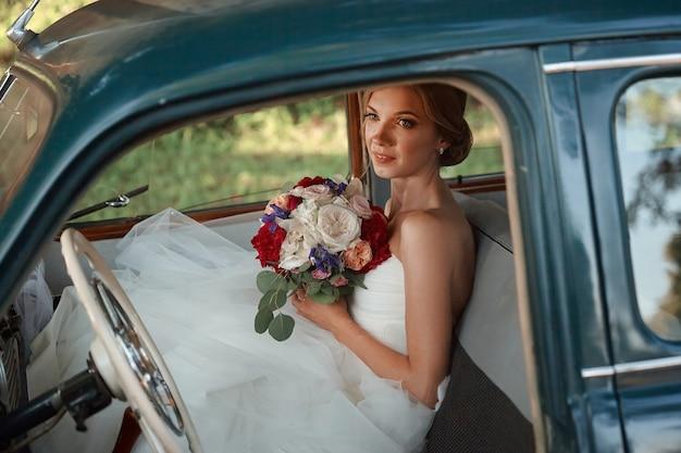 Piękna panna młoda z bukietem ślubnym siedzi w samochodzie