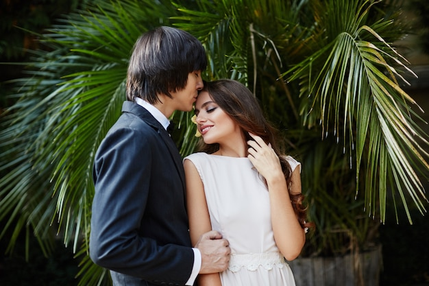 Piękna panna młoda z długimi kręconymi włosami i oblubieńcem stojącym blisko siebie na tle zielonych liści, zdjęcie ślubne, piękna para, dzień ślubu, portret z bliska.