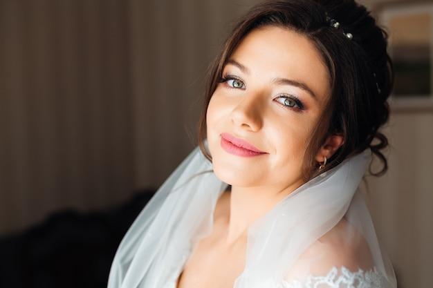 Piękna panna młoda z fryzurą ślubną mody iz welonem. uśmiecha się i patrzy w obiektyw aparatu
