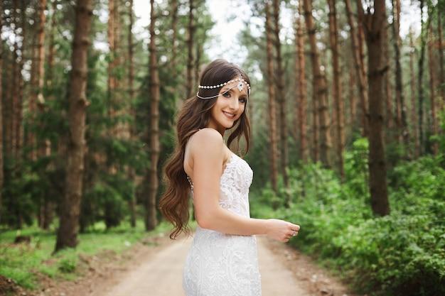 Piękna panna młoda z fryzurą ślubną z biżuterią w koronkowej sukience z bukietem kwiatów w dłoniach i pozuje w lesie wczesnym rankiem