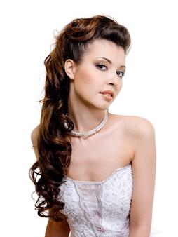 Piękna panna młoda z nowoczesną stylową fryzurą ślubną
