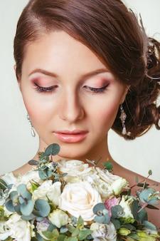 Piękna panna młoda z ornamentem we włosach i bukietem patrząc w dół.