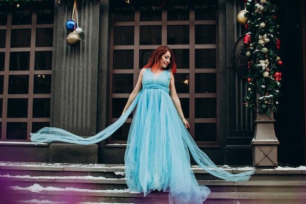 Piękna panna młoda z rudymi włosami w niebieskiej długiej sukni na tle miasta