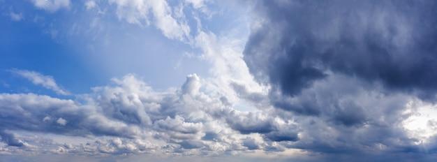 Piękna panorama błękitnego nieba z ciemnymi chmurami w świetle dziennym.