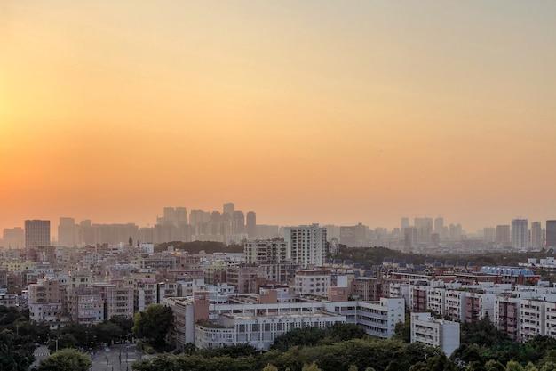 Piękna panorama budynków miasta pod pomarańczowym niebem o zachodzie słońca