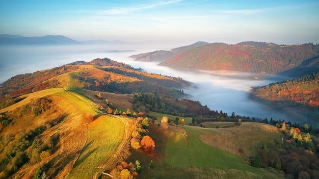 Piękna panorama górska jesień. poranna gęsta mgła pokrywa dolinę widok z lotu ptaka