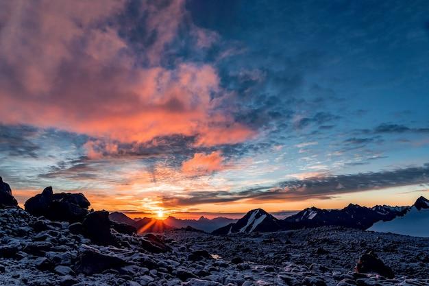 Piękna panorama wysokich gór skalistych z potężnymi lodowcami na tle błękitnego nieba i chmur o wschodzie słońca