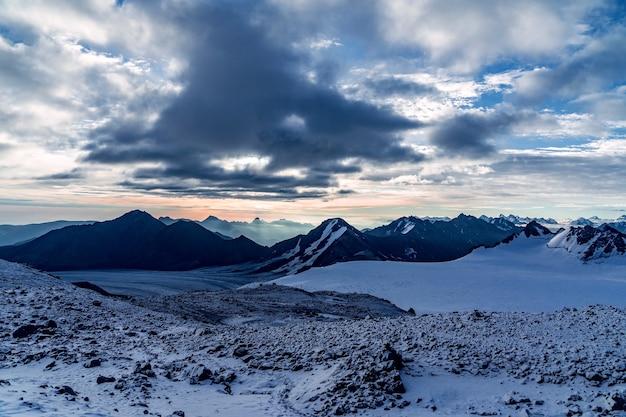 Piękna panorama wysokich gór skalistych z potężnymi lodowcami na tle błękitnego nieba i chmur