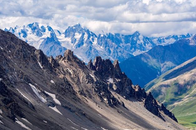 Piękna panorama wysokich skalistych gór z potężnymi lodowcami i ośnieżonymi szczytami na tle błękitnego nieba i chmur