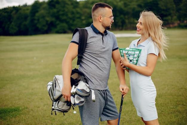 Piękna para bawić się golfa na polu golfowym