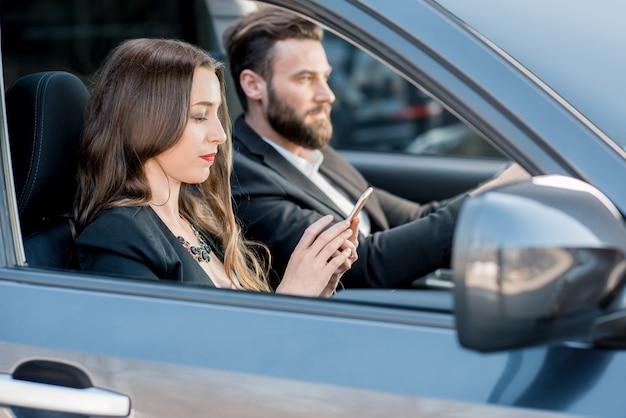 Piękna para biznesowa prowadząca samochód po mieście