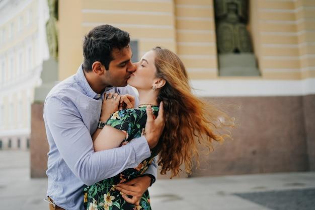 Piękna para całuje na ulicy z zamkniętymi oczami. młody brazylijski mężczyzna z pasją ściska swoją dziewczynę. kochankowie w mieście.