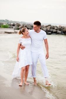 Piękna para chodzi na morzu w biel ubraniach
