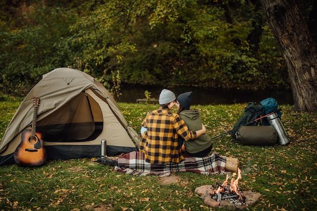 Piękna para ciesząca się przyrodą w pobliżu namiotu siedzącego na kłodzie