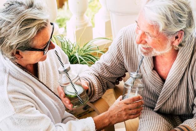 Piękna para dwóch dojrzałych dorosłych i seniorów, którzy bawią się i piją koktajl między - kurortem w hotelu - farmą piękności