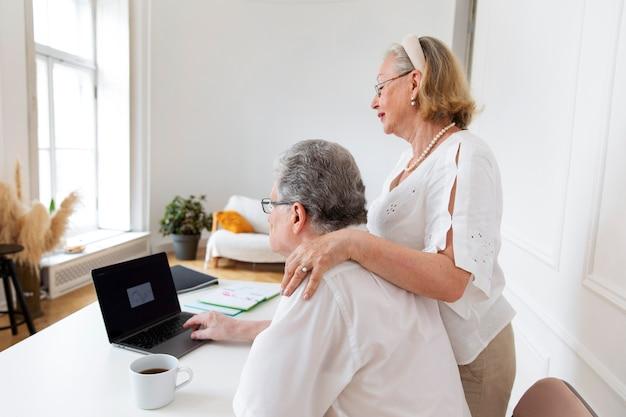 Piękna para dziadków uczy się korzystać z urządzenia cyfrowego