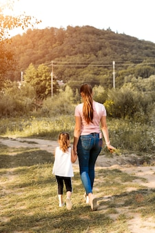 Piękna para dziecko dziewczynka z matką chodzą w wiosenny ogród z różowe kwiaty róż kwiaty, zachód słońca