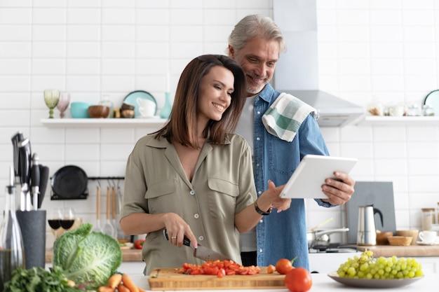 Piękna para korzystająca z cyfrowego tabletu i uśmiechająca się podczas gotowania w kuchni w domu