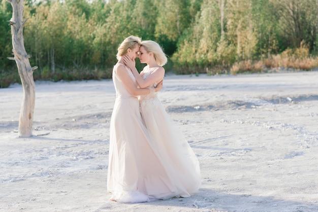Piękna para lesbijek na piaszczystej plaży
