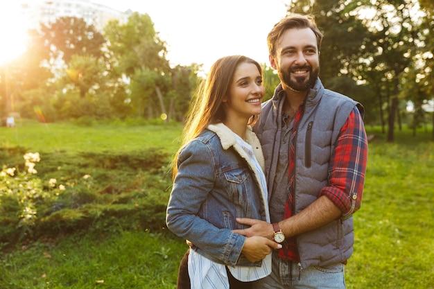Piękna para mężczyzna i kobieta ubrani w codzienny strój przytulający się podczas wspólnego spaceru w zielonym parku