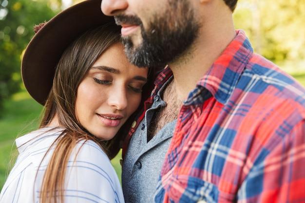 Piękna para mężczyzna i kobieta ubrani w codzienny strój przytulający się razem podczas spaceru w zielonym parku
