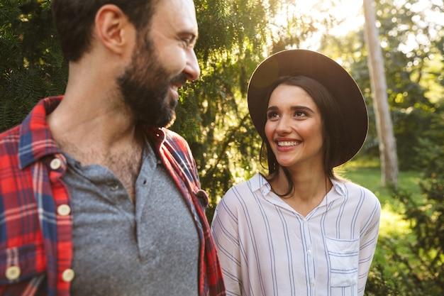 Piękna para mężczyzna i kobieta ubrani w codzienny strój, uśmiechający się, patrząc na siebie w zielonym parku