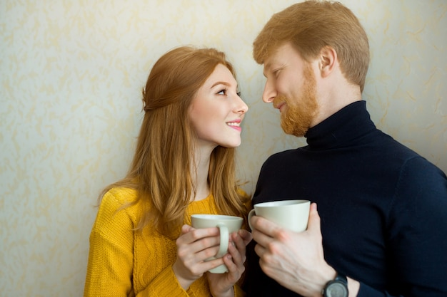 Piękna para mężczyzna i kobieta z kubkami herbaty
