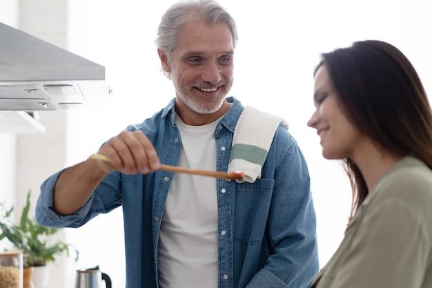 Piękna para. mężczyzna karmi żonę i uśmiecha się podczas gotowania w kuchni w domu