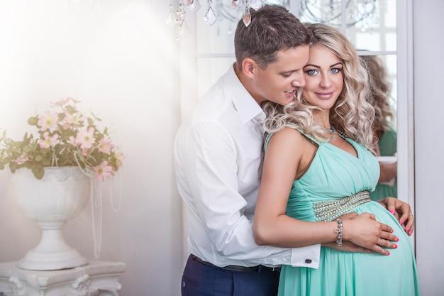 Piękna para, młoda kobieta w ciąży i mężczyzna, przytulanie z miłością, we wnętrzu domu