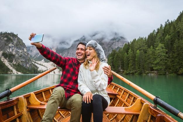 Piękna para młodych dorosłych odwiedzających alpejskie jezioro w braies we włoszech