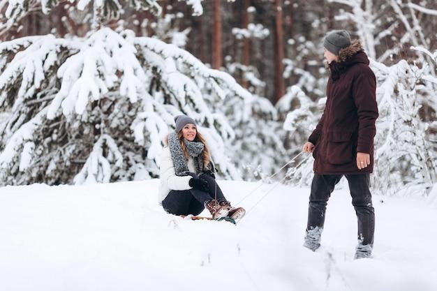 Piękna para na sankach, zabawy, zimowy dzień śniegu