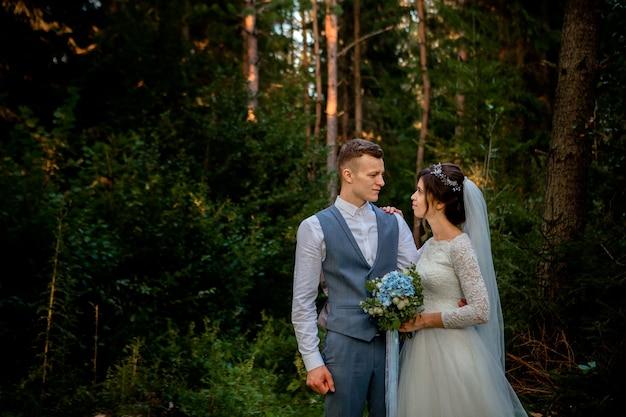 Piękna para nowożeńców spaceru w lesie. nowożeńcy. panna młoda i pan młody trzymający się za rękę w sosnowym lesie, zdjęcie na walentynki.
