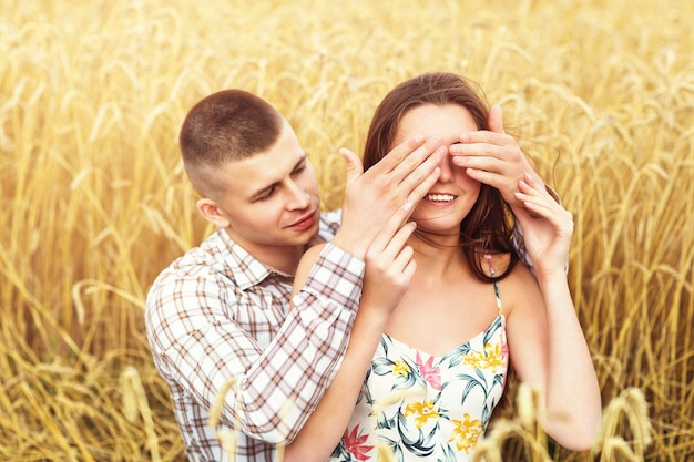Piękna para odpoczywa na polu pszenicy kochająca dziewczyna i jej chłopak razem