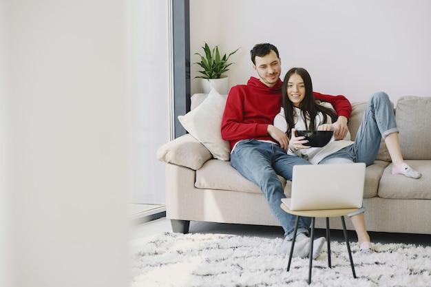 Piękna para ogląda film na kanapie