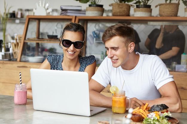 Piękna para ogląda filmy online, siedzi przy stoliku kawiarnianym z laptopem, jedzeniem i napojami, korzystając z bezpłatnego bezprzewodowego połączenia z internetem i uśmiecha się