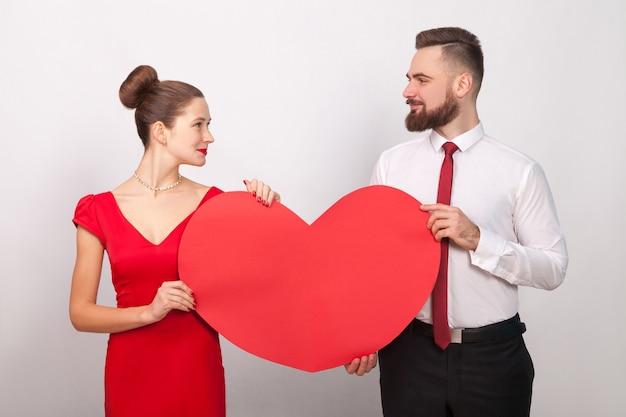 Piękna para patrząc na siebie, trzymając czerwone serce, ich miłość. wewnątrz, studio strzał, na białym tle na szarym tle
