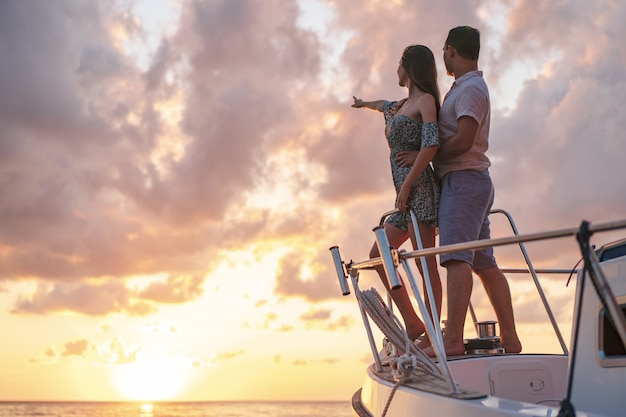 Piękna para patrząca na zachód słońca z jachtu