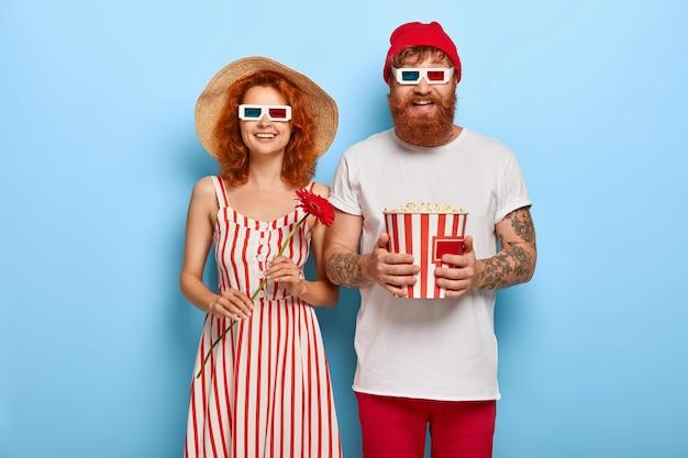 Piękna para patrzy radośnie na ekran, ogląda zabawny film, śmieje się z pozytywnych emocji
